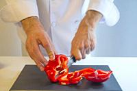 Chef cutting a red pepper in slices.