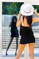 Slender-fit teen girl is posing before glass window adjusting her White hat
