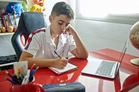 teenager teaching online classes and doing his homework in his study room