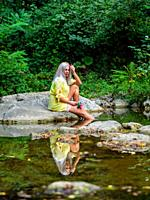 Attractive blonde woman on a Green forest river with bunch of flowers in hand