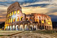 Illuminated Roman Coliseum under the clouds at sunrise, Italy.