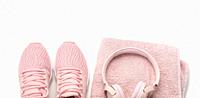 pair of pink textile sneakers, wireless headphones and a textile pink towel on a white background. Set for sports, running.