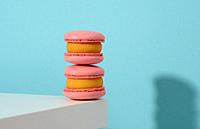 baked pinke round macarons on a blue background, delicious dessert.
