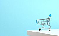 empty miniature shopping cart on blue background. Seasonal sale, copy space, online shopping.