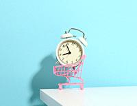 miniature metal shopping cart on wheels and in the middle of a round alarm clock on a white table. Start of discounts, sale.
