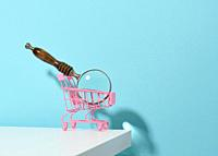miniature metal pink trolley and wooden magnifier on a light blue background. The concept of search and selection of purchases, savings.