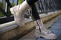 Woman in stylish leather boots and jeans outdoors. Close up of female legs in fashion footwear.