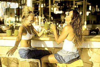 Two women drinking cocktails at bar, Hersonissos, Crete, Greece.