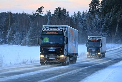 Salo, Finland - January 18, 2019: Two Customised MAN semi trailer trucks of Stengel LT haul goods through winter scenery at dusk in South of Finland.