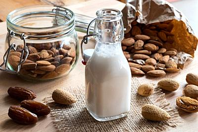 A bottle of almond milk with whole (unshelled) and shelled almonds and dates.