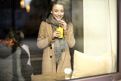 young teenage woman behind window drinking takeaway orange juice in café, plastic cup, in Cottbus, Brandenburg, Germany