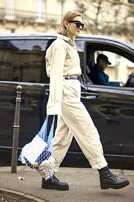 fashionable blogger woman spotted on street at paris fashion week, wearing latest fashion trend, beige overall jumpsuit and net handbag, in Paris, Fra...
