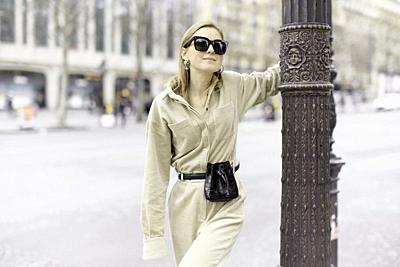 fashionable woman at lamp post at street during fashion week, in Paris, France.