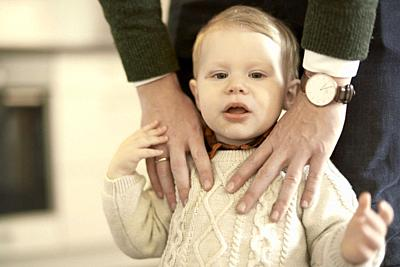 baby toddler child with hands of caring father on him, in Cottbus, Brandenburg, Germany.