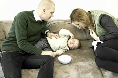 parents with baby toddler child on couch in living room at home, in Cottbus, Brandenburg, Germany.