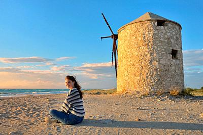 Teen girl and Old windmill ai Gyra beach, Lefkada.