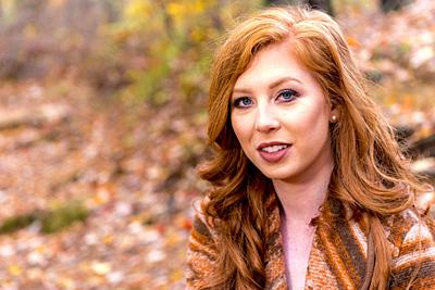 Portrait of a 25 year old redheaded woman in a forest setting.