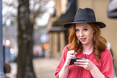 Portrait of a 25 year old redheaded woman wearing a black hat in an urban setting.