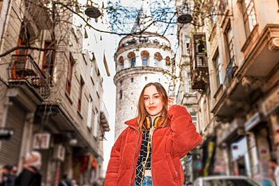 Beautiful attractive happy young trendy girl poses with view of Galata tower in Beyoglu,Istanbul,Turkey.