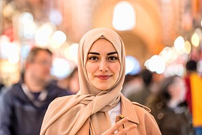 Portrait of beautiful Muslim woman in headscarf and fashionable modern clothes looking at camera. Modern Muslim women lifestyle business or travel tou...