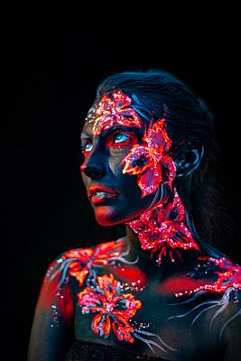 Conceptual face art with shining flowers painted in fluorescent colors isolated on black background.