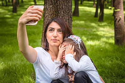 Young mom and little girl takes selfie together. Little girl hides her face. Photo of young mother and her daughter having selfie on green grass.