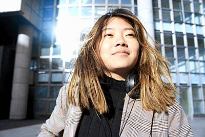 young confident Asian woman in business district in Paris, France.
