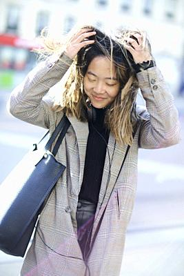 young unkempt Asian woman playing with hairs at street, in Paris, France.