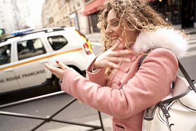 woman moving arms at street in city, in Paris, France.