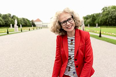 smiling senior woman (67 years old) in park, in Nymphenburg, Munich, Germany.