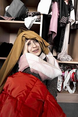 young woman overwhelmed by her clothes, in front of wardrobe