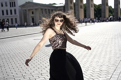 young woman dancing at Pariser Platz next to Brandenburg Gate, in Berlin, Germany.