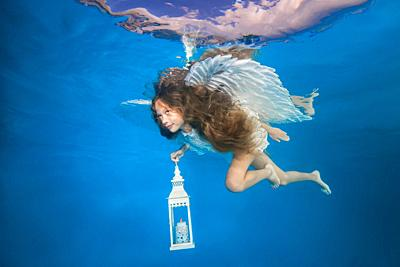 White angel with a flashlight underwater. Underwater girls pictures.