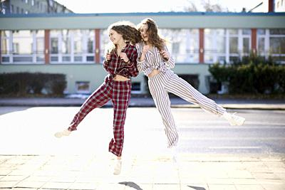 two happy women jumping against each other, wearing pyjamas at street