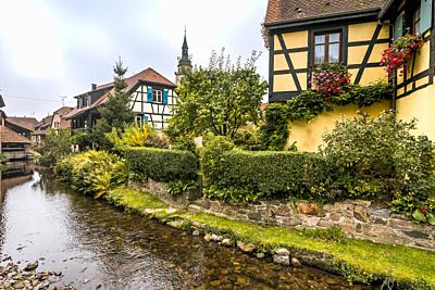 old village Andlau, Alsace Wine Route, France, half-timbered houses and flower decoration at the brook side.