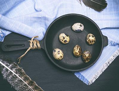 raw quail eggs in the shell lie in a black cast-iron frying pan, top view.
