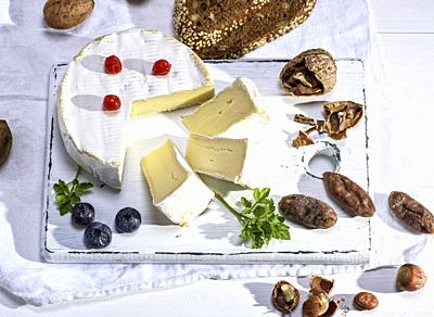 round Camembert cheese on a white wooden board, next to sausage and nuts, white wooden table, top view.