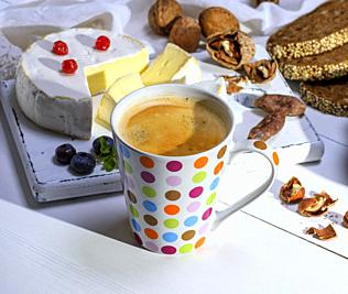 black coffee in a white ceramic mug in a multi-colored circle on a wooden table, breakfast for one.