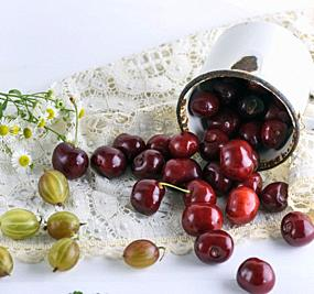 scattered ripe red berries cherries from a white iron mug on a table.
