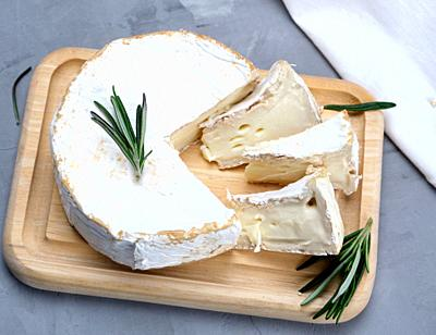 round brie cheese on a wooden board, gray background , top view.