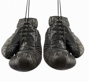 pair of very old vintage black leather boxing gloves hanging on a rope, object isolated.