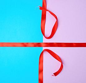 red satin ribbon on a colored background, imitation of tying and packing a gift.