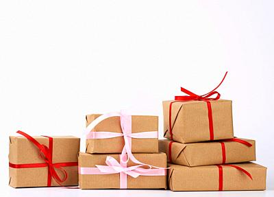 stack of gifts in boxes wrapped in brown kraft paper and tied with silk ribbon on a white background. Festive concept, copy space.