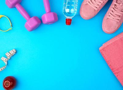 plastic purple dumbbells, sportswear, water, pink sneakers on a blue background, fitness kit, flat lay, copy space.