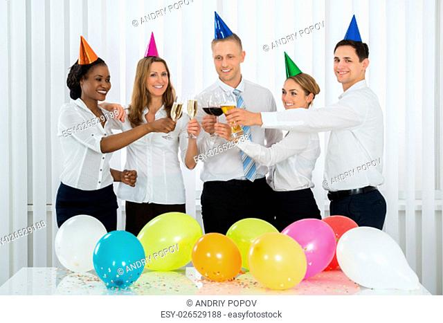 Group Of Happy Businesspeople Toasting With Champagne At The Party