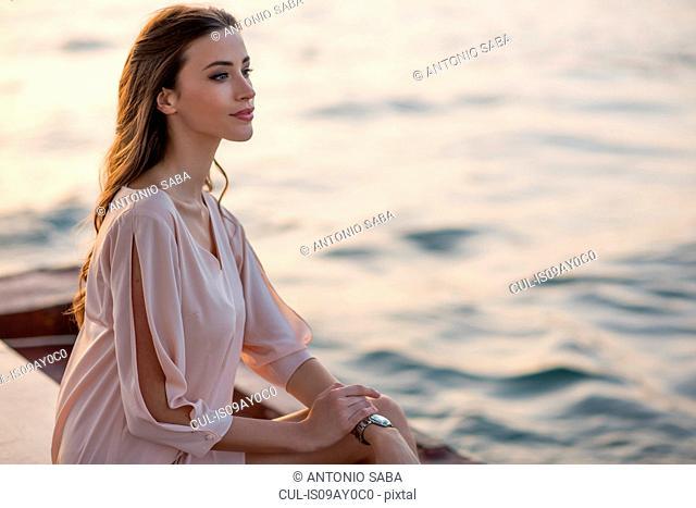 Woman gazing from boat at Dubai marina, United Arab Emirates
