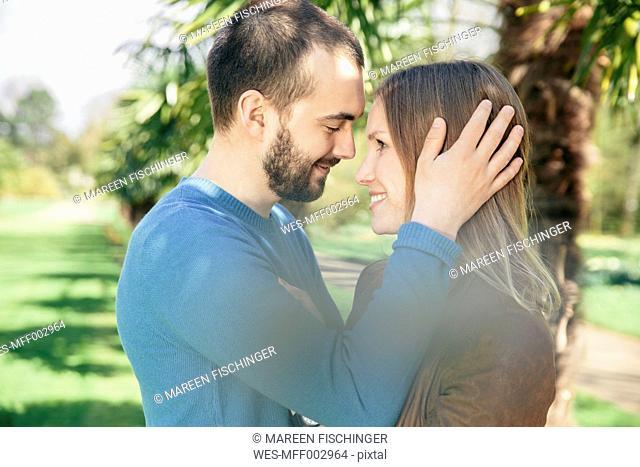 Happy couple face to face in a botanical garden
