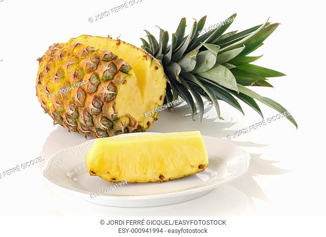 Cut pineapple and leaves on white background