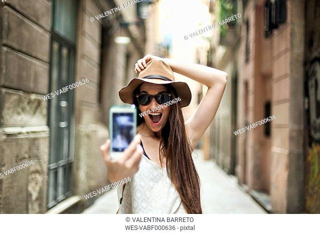 Young tourist discovering streets of Barcelona, taking selfie