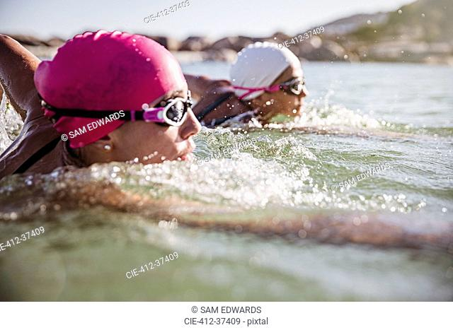 Female open water swimmers swimming in sunny ocean